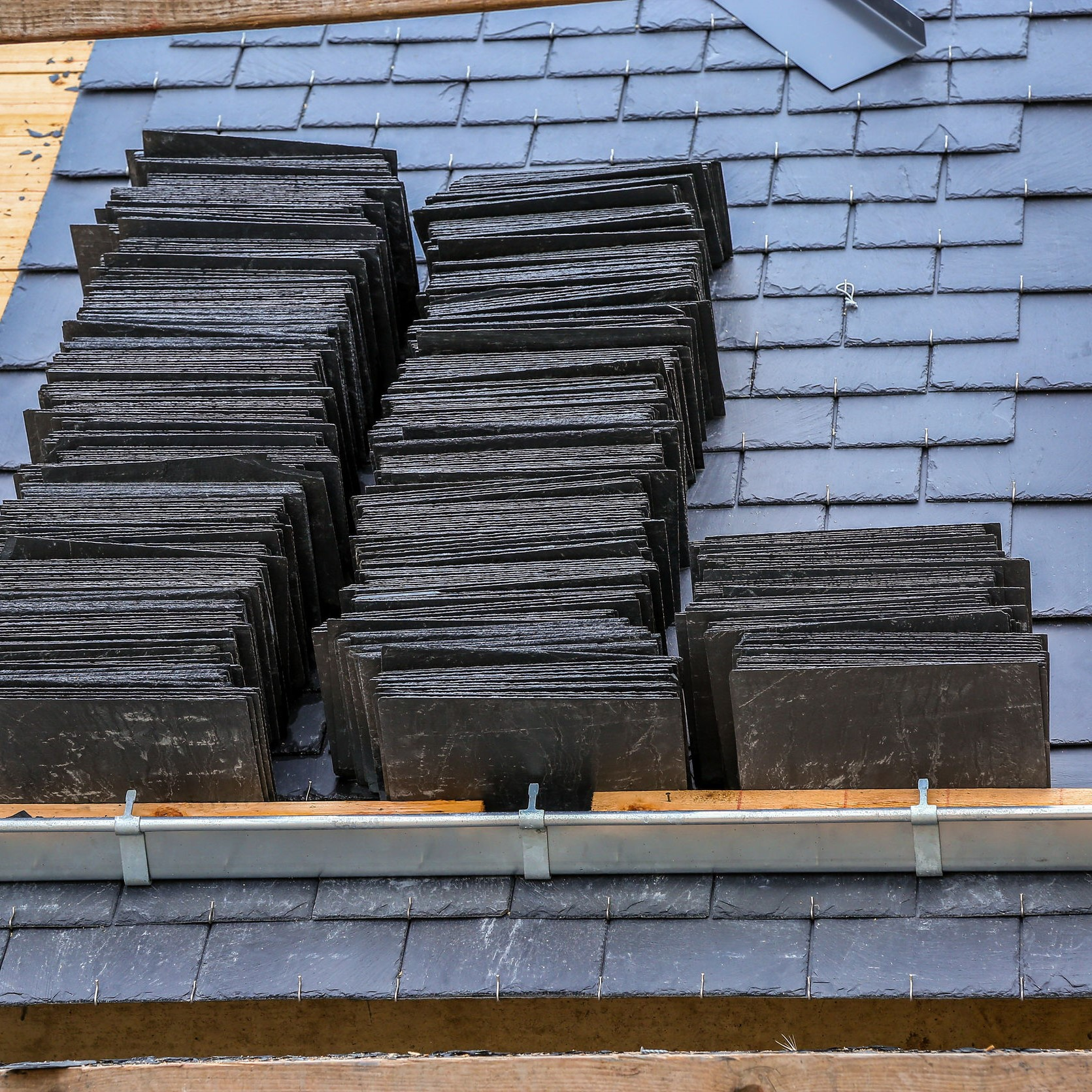 Eco Slate tiles being installed on a roof.