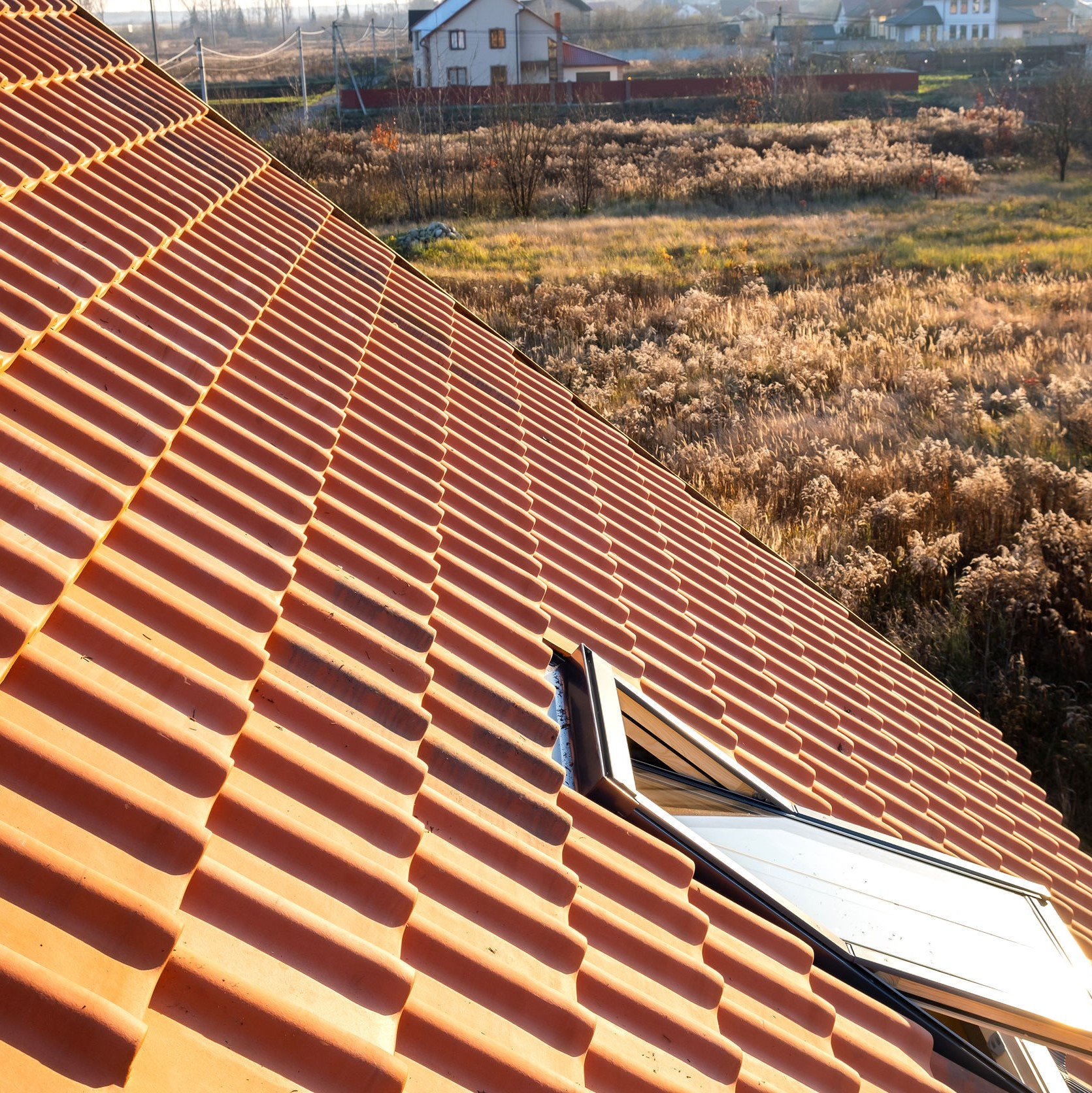 A tile roof on a home in the country.